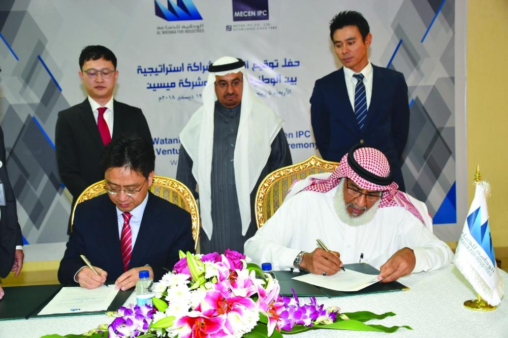 Jae Chul Park, Executive Director of MECEN IPC, South Korea, and Eng. Ibrahim I. Behairi, CEO of Al Watania Industries, sign the JV agreement. Sheikh Fahad Bin Sulaiman Al Rajhi, Vice Chairman, Al Watania Industries can be seen in the background.