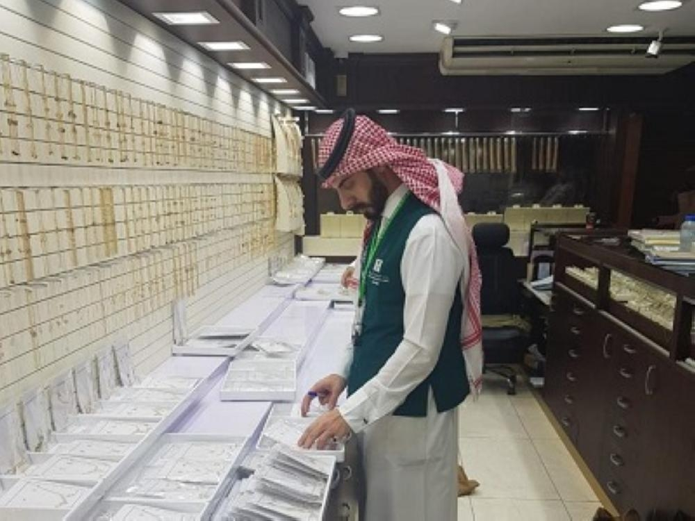 A Ministry of Commerce inspector verifies jewelry displayed at one of the two gold shops.