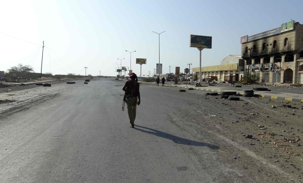 A Yemeni fighter of the pro-government forces walks with a rifle in the Red Sea port city of Hodeida. — AFP