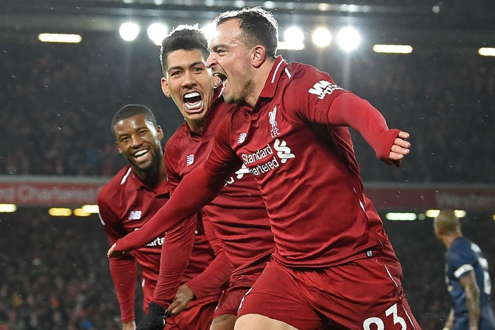 Liverpool's Xherdan Shaqiri (R) celebrates with Georginio Wijnaldum (L) and Roberto Firmino after scoring their third goal during the English Premier League football match against Manchester United at Anfield in Liverpool Sunday. — AFP