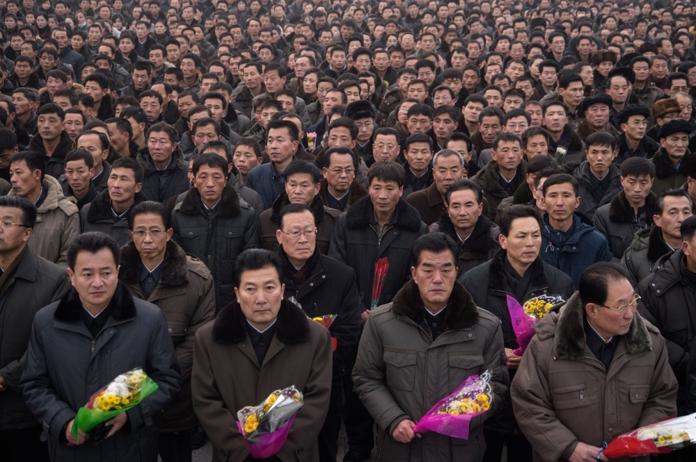 Pyongyang residents prepare to lay flowers at the statues of late North Korean leaders Kim Il Sung and Kim Jong Il during National Memorial Day on Mansu Hill in Pyongyang on Monday. — AFP