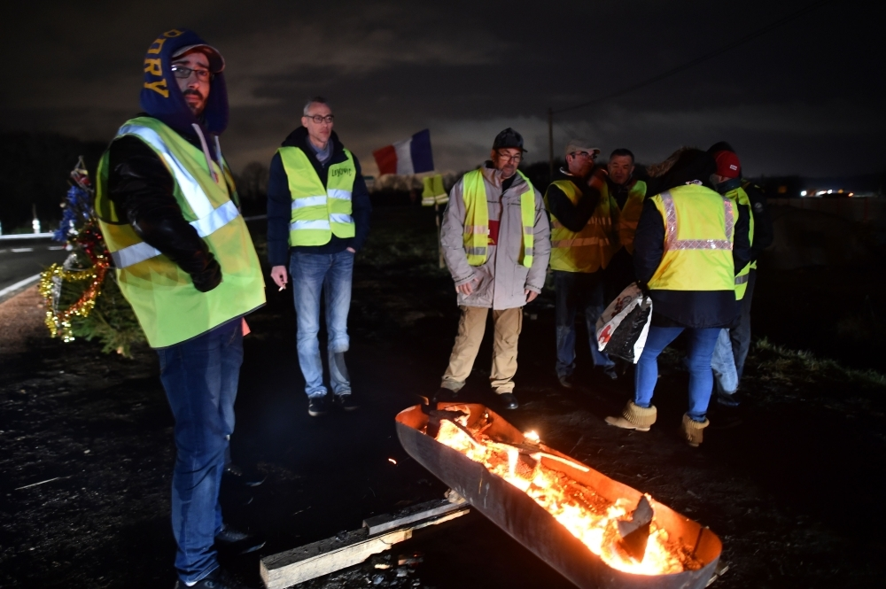 Yellow vests protestors stand by a fire next to a Christmas tree on the edge of one of the access roads to the South Le Mans ring road, France, on Sunday. — AFP