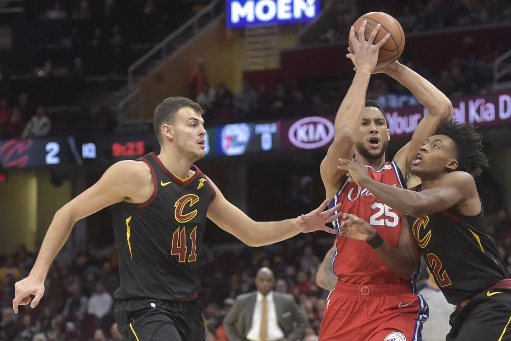 Philadelphia 76ers' guard Ben Simmons drives between Cleveland Cavaliers' center Ante Zizic (L) and guard Collin Sexton during their NBA game at Quicken Loans Arena in Cleveland Sunday. — Reuters