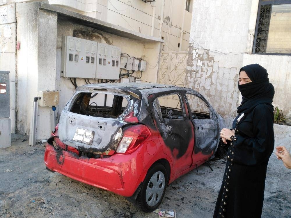 Angry and frustrated, Nurhan Bassam stands beside her burned out car.