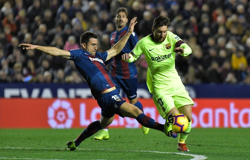 Levante's defender Sergio Postigo (L) tackles Barcelona's Lionel Messi during their Spanish League football match at the Ciutat de Valencia Stadium in Valencia Sunday. — AFP