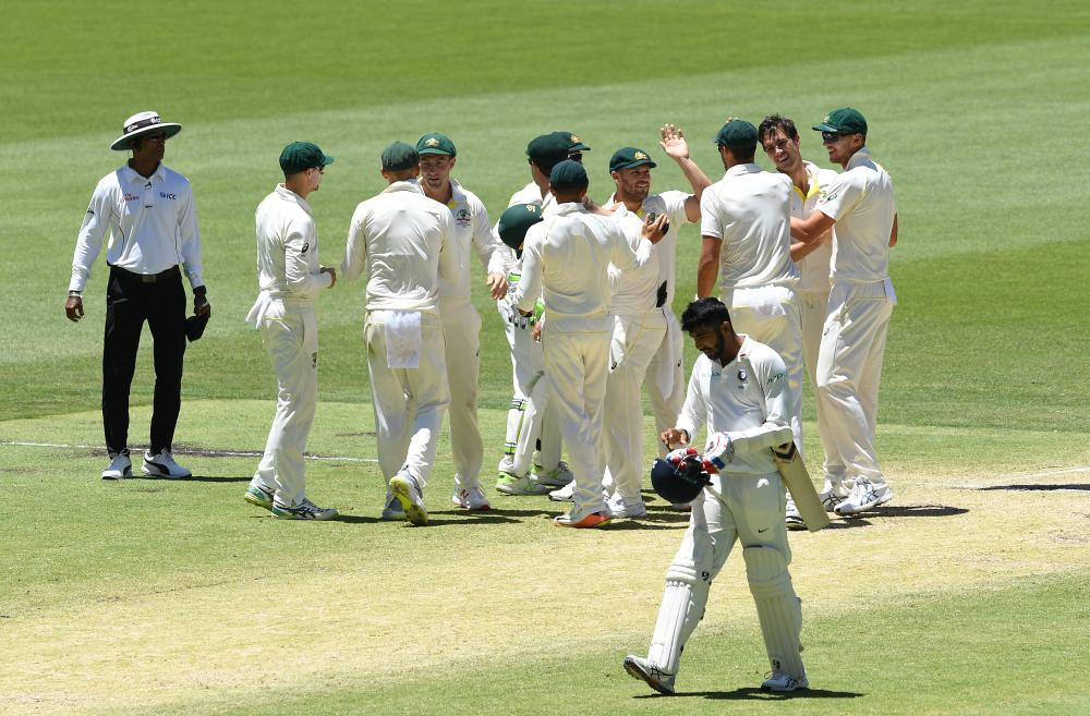 India's Jasprit Bumrah walks as Australia's players celebrate after they defeated India on day five of the second Test match at Perth Stadium. — Reuters