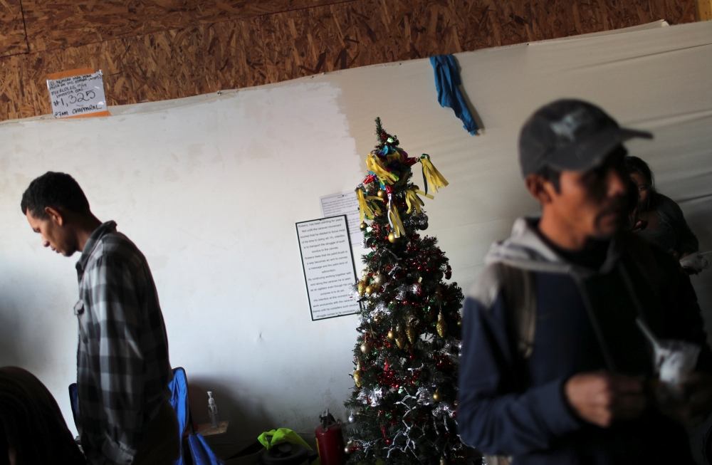 Migrants, part of a caravan of thousands from Central America trying to reach the United States, stand next a Christmas tree at the temporary shelter in Tijuana, Mexico, on Tuesday. — Reuters