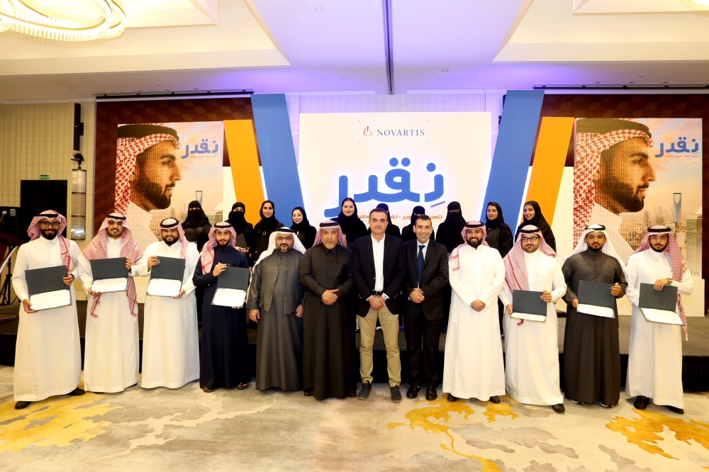 Saudi pharmacy graduates who completed the training with company officials.