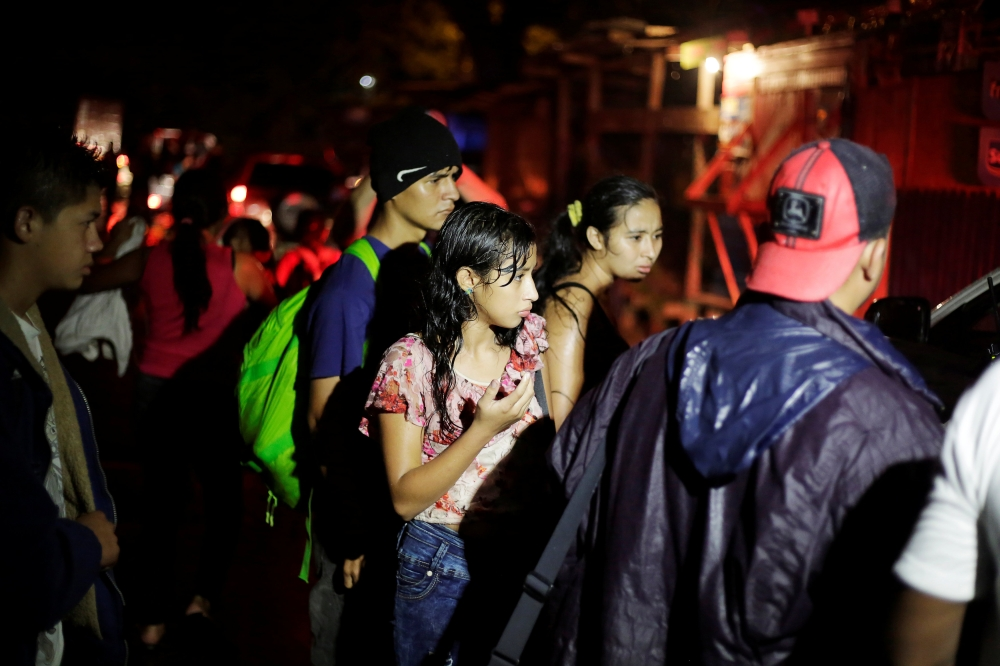 Hondurans, part of a new caravan of migrants traveling towards the United States, are seen as they wait to catch a ride in Cofradia, Honduras, on Monday. — Reuters