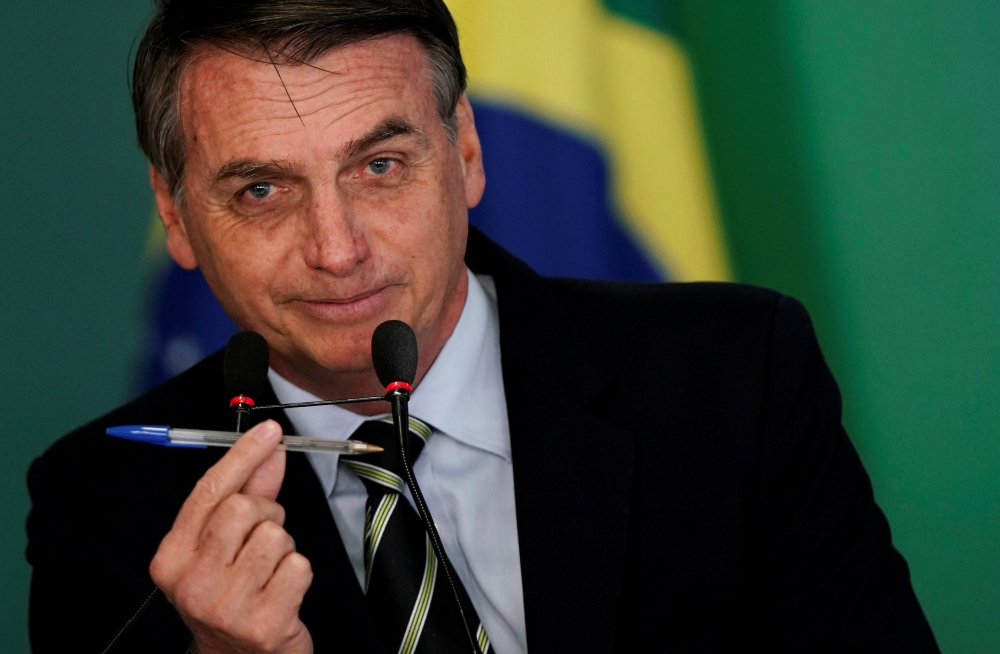 Brazil's President Jair Bolsonaro shows a pen during a signing ceremony of the decree which eases gun restrictions in Brazil, at the Planalto Palace in Brasilia, Brazil, on Tuesday. — Reuters