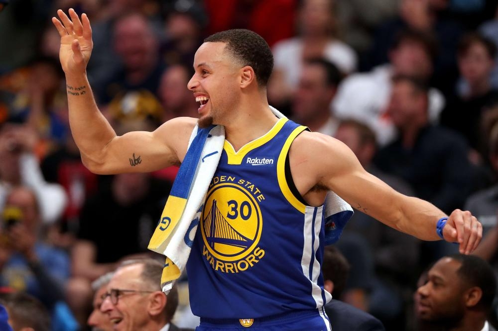 Stephen Curry of the Golden State Warriors celebrates on the bench against the Denver Nuggets during their NBA game at the Pepsi Center in Denver Tuesday. — AFP