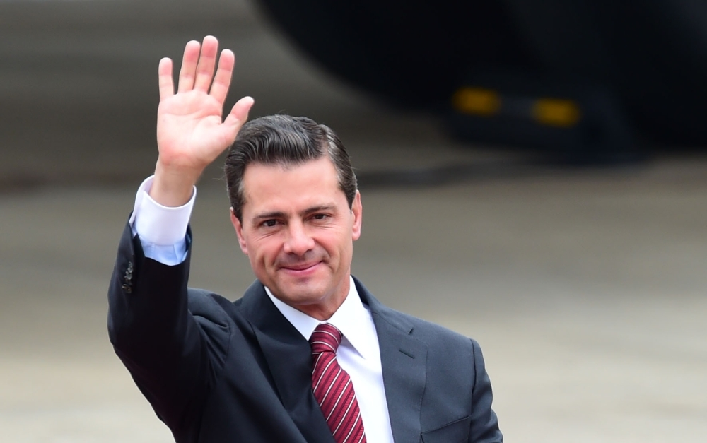 Former Mexican President Enrique Pena Nieto waves upon arrival at Ezeiza International airport in Buenos Aires province, Argentina, in this Nov. 29, 2018 photo. — AFP