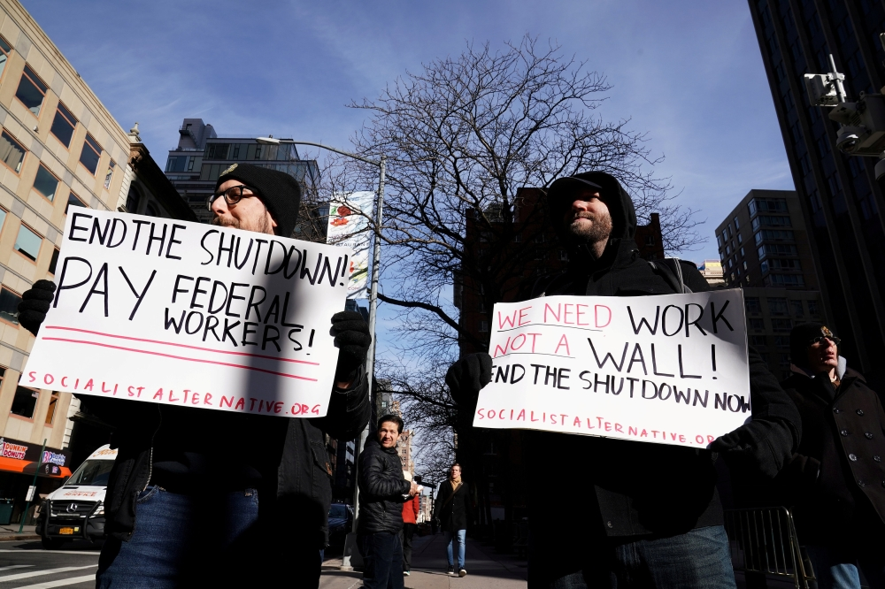 Protesters hold signs during a rally outside a closed federal building in the Manhattan borough of New York City, New York, on Tuesday. — Reuters