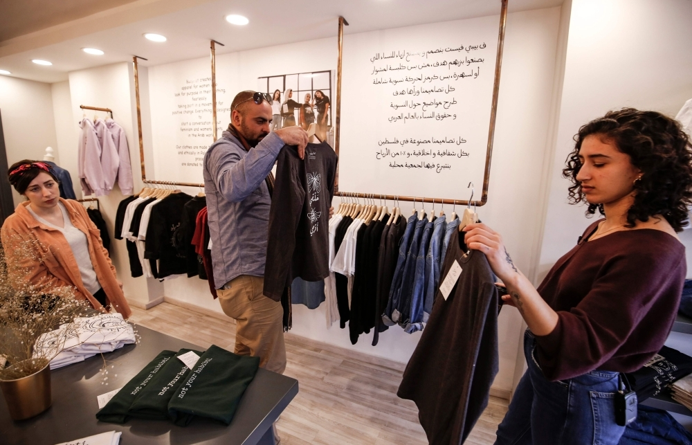 Palestinian fashion designer Yasmeen Mjalli (right) arranges clothes in her shop where her label collection
