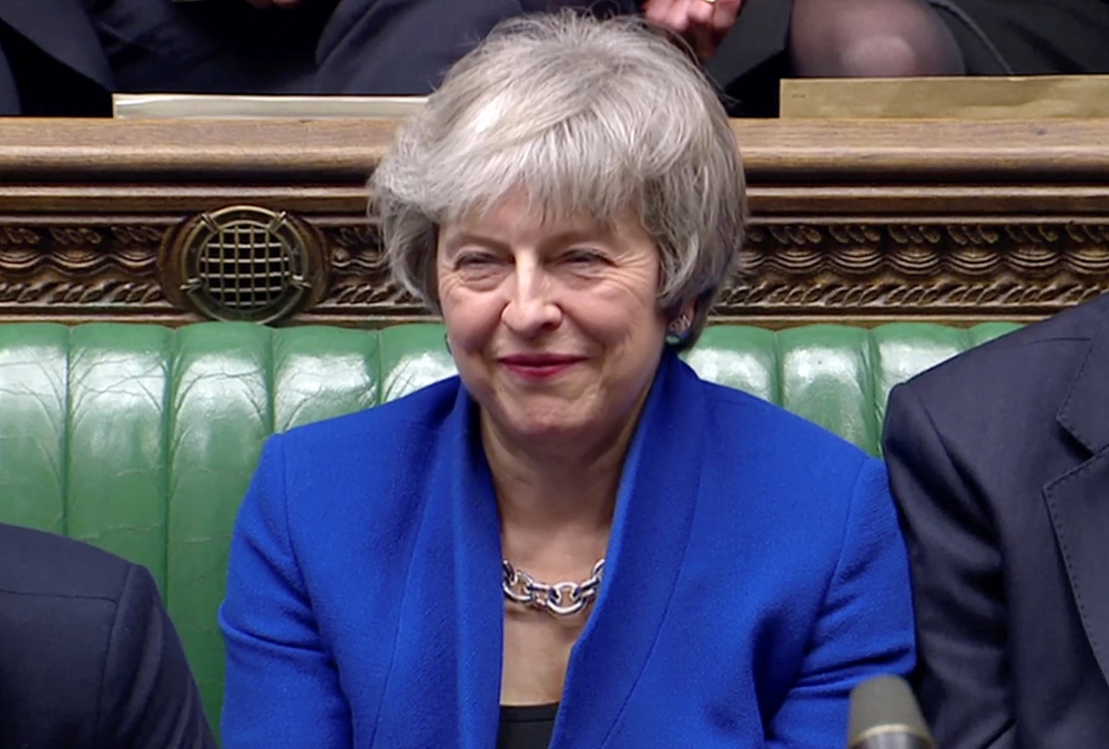 British Prime Minister Theresa May reacts as Jeremy Corbyn speaks, after she won a confidence vote, after Parliament rejected her Brexit deal, in London, Britain, on Wednesday, in this screen grab taken from video. — Reuters