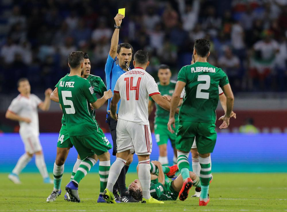 Iran's Saman Ghoddos is shown a yellow card by referee Ravshan Irmatov during their Asian Cup match against Iraq at Al-Maktoum Stadium in Dubai Wednesday. — Reuters