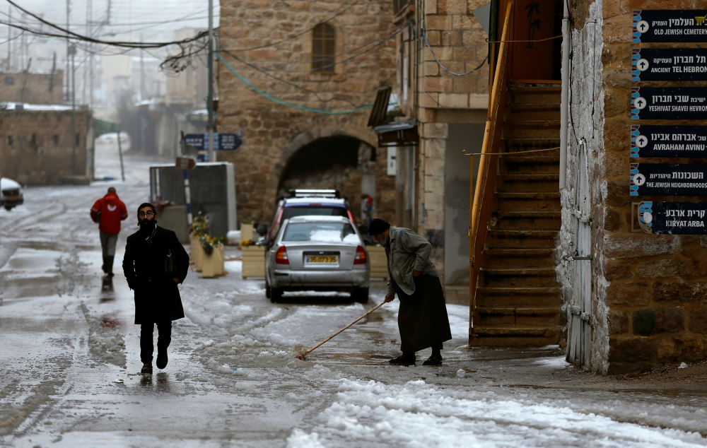 A Jewish settler walks as a Palestinian man removes snow during a winter storm in Hebron, in the Israeli-occupied West Bank, on Thursday. — Reuters
