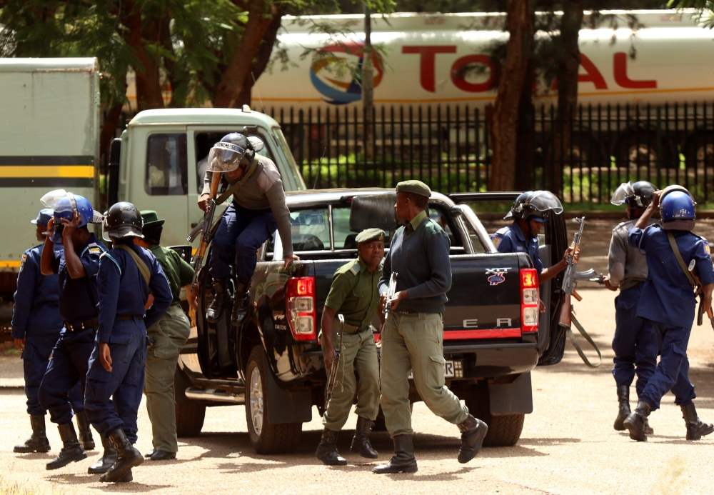 Police stand guard as people arrested during protests appeal in court in Harare, Zimbabwe, on Friday. — Reuters