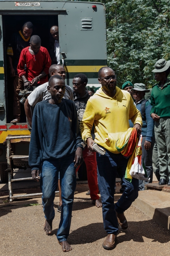 Zimbabwean cleric and activist Pastor Evan Mawarire (right) exits a prison truck as he arrives at the Harare Magistrates Court in Harare on Saturday, for a court hearing on subversion charges. — AFP