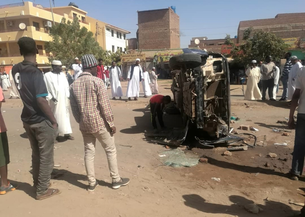 Sudanese men gather around a pickup truck which was overturned during clashes amidst an anti-government protest in the capital Khartoum on Friday. — AFP