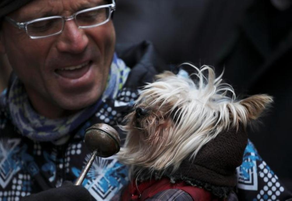 A dog owner brings his pet to a Madrid curch to be blessed. — Reuters