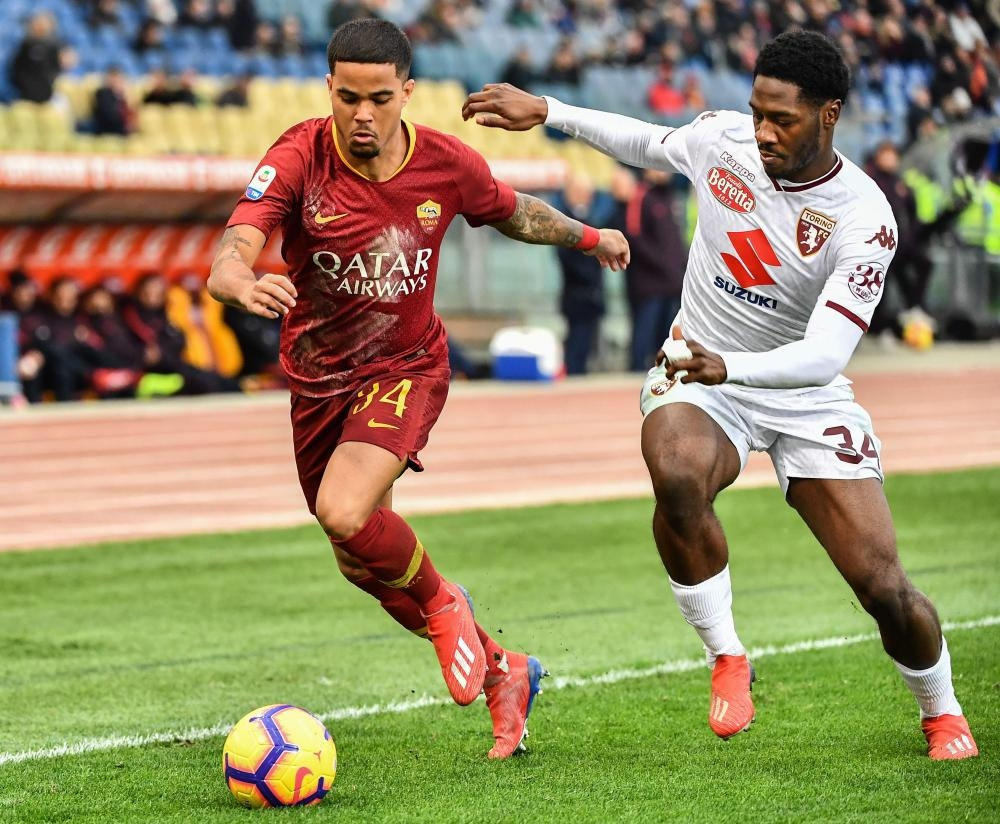 AS Roma's forward Justin Kluivert (L) outruns Torino's defender Ola Aina during the Italian Serie A football match at the Olumpic Stadium in Rome Saturday. — AFP