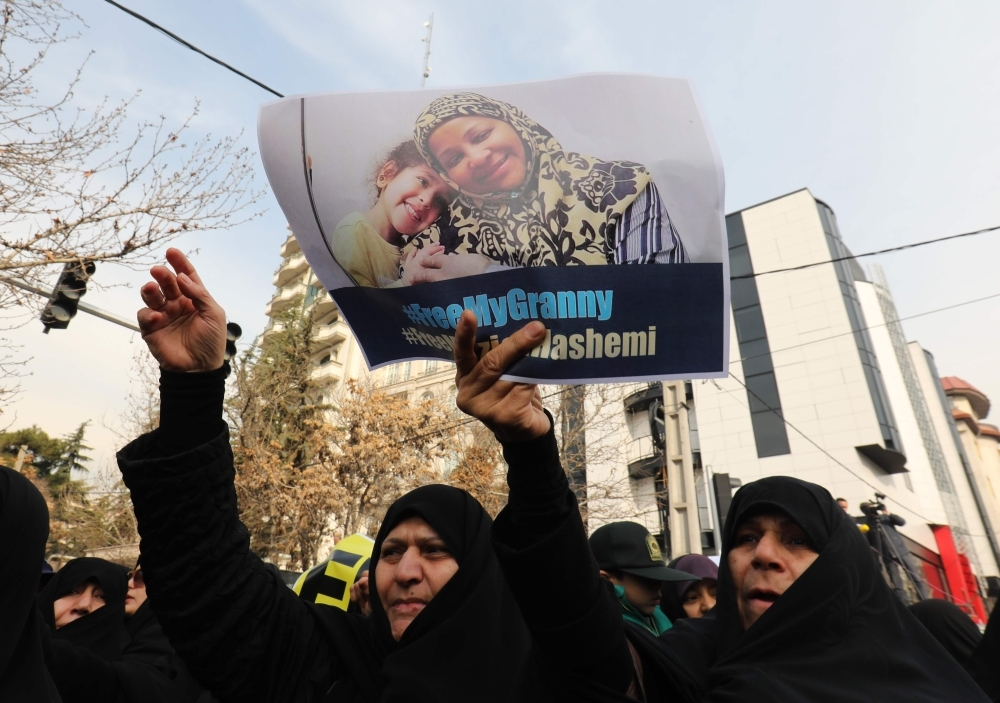 Iranians hold banners bearing messages that call for the release of US-born journalist Marzieh Hashemi, in front of the Swiss embassy in the capital Tehran on January 20, 2019.  The head of Iran's English-language Press TV said that one of its journalists and her son have been detained in the United States on unspecified charges. Hashemi was arrested on arrival at St Louis Lambert International Airport on Januarey 13, 2019, according to family and friends cited by Press TV. / AFP / ATTA KENARE