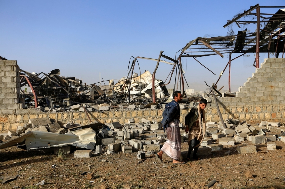 Civilians inspect the damage at a factory after a reported airstrike by Saudi-led coalition in the Yemeni capital Sanaa, on Sunday. — AFP
