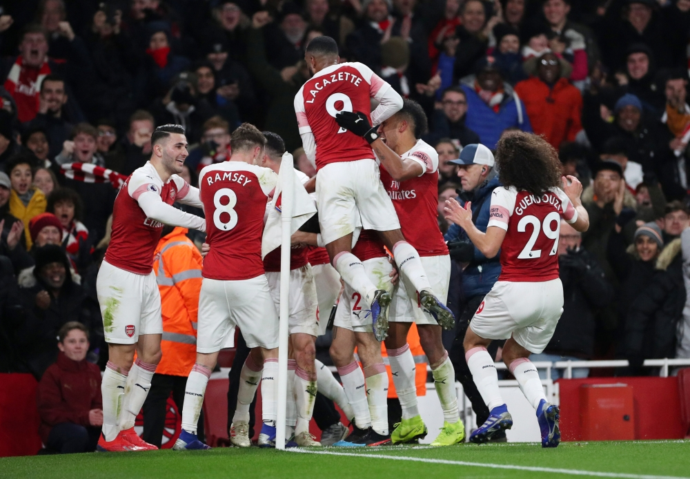 Arsenal's players celebrate after Laurent Koscielny (hidden) scored against Chelsea during their Premier League match at Emirates Stadium, London, Saturday. — Reuters