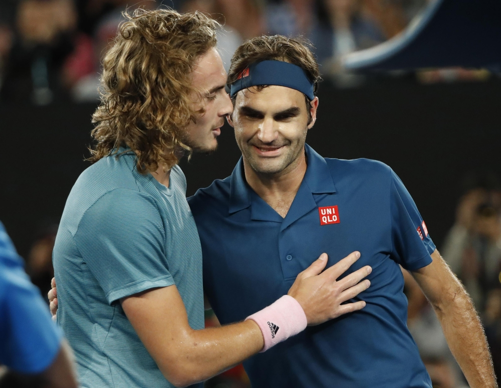 Switzerland's Roger Federer and Greece's Stefanos Tsitsipas greet each other after their match at the Australian Open Tennis Tournament in Melbourne Sunday. — Reuters