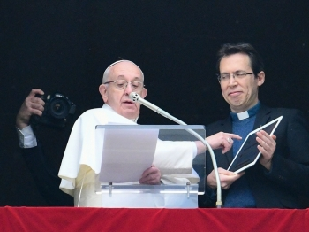 Pope Francis points to a tablet computer as he invites the faithful to download the 'Click to Pray' app, from the window of the Apostolic Palace overlooking St. Peter's square in the Vatican during the weekly prayer on Sunday.  — AFP