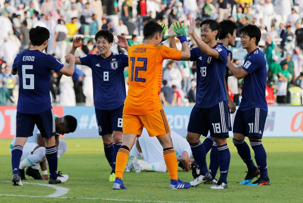 Japan's players celebrate at the end of the AFC Asian Cup match against Saudi Arabia at Sharjah Stadium Monday. — Reuters
