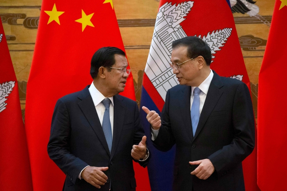 Cambodia's Prime Minister Hun Sen, left, chats with China's Premier Li Keqiang during a signing ceremony at the Great Hall of the People in Beijing on Tuesday. — AFP