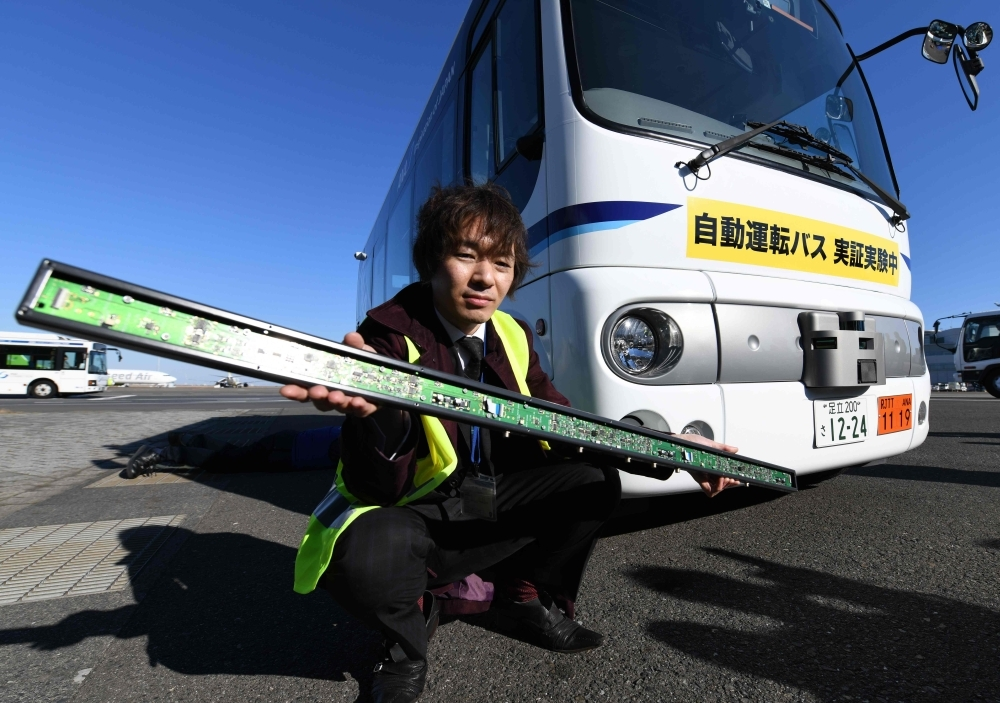 An officer shows off a magnetic sensor module in front of a driverless bus during an open test drive demonstration at Tokyo's Haneda International airport on Tuesday. — AFP