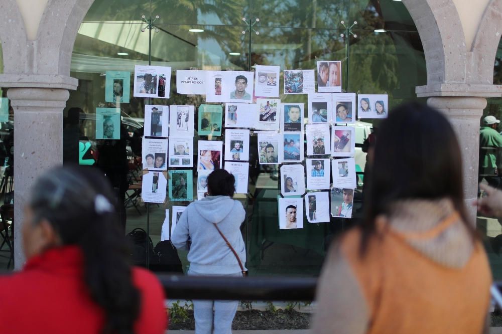 Residents look at pictures of people missing after an explosion of a fuel pipeline ruptured by oil thieves, in the municipality of Tlahuelilpan, state of Hidalgo, Mexico, on Monday. — Reuters