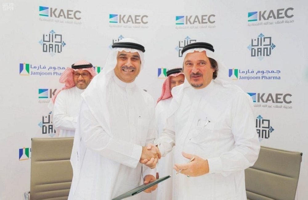 Representatives of the King Abdullah Economic City and Jamjoom Pharma exchange documents after signing the hospital agreement.