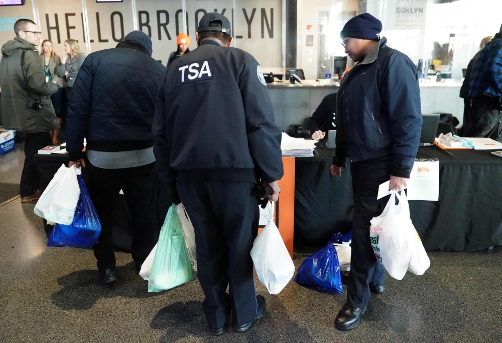 Furloughed Transportation Security Administration (TSA) employees and others leave the Barclays Center with bags of food as the Food Bank For NYC holds food distribution for federal workers impacted by the government shutdown in Brooklyn, New York, on Tuesday. — AFP