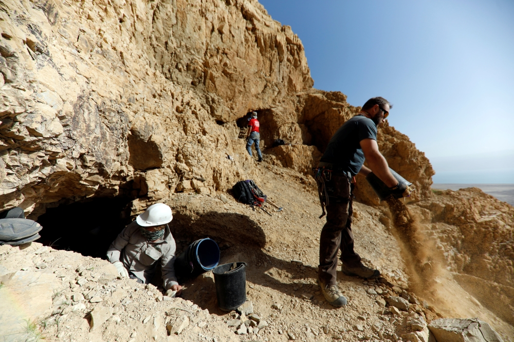 Volunteers and archeologists work at a dig near caves in the Qumran area in the Israeli-occupied West Bank.