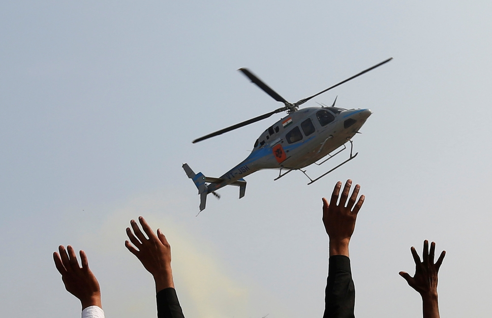 Supporters wave toward a helicopter carrying Keshav Prasad Maurya, the Uttar Pradesh state's president for the ruling Bharatiya Janata Party (BJP), during an election campaign rally in Bah, in the central state of Uttar Pradesh, India, in this Feb. 2, 2017 file photo. — Reuters