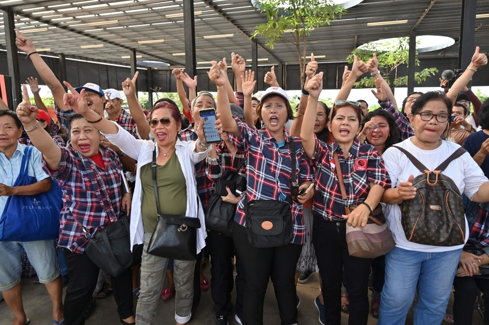 Indonesian supporters of Jakarta's former governor Basuki Tjahaja Purnama alias Ahok sing along to celebrate his release from prison in Jakarta on Thursday. — AFP