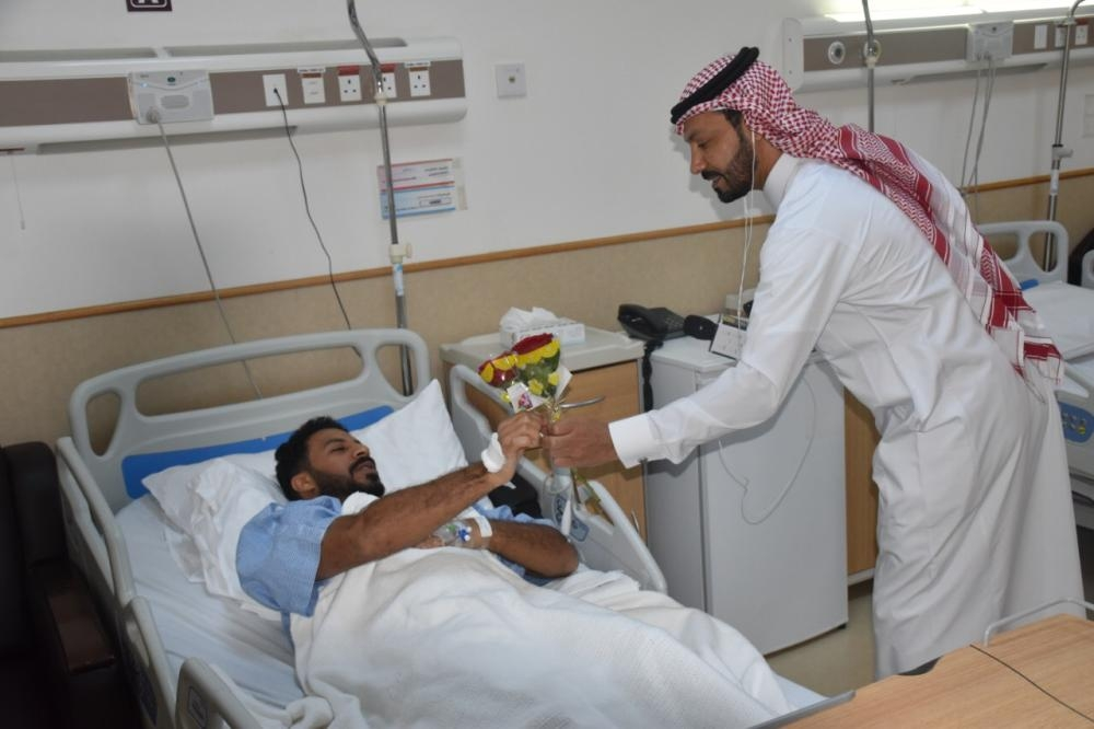A member of the media delegation presents a gift to one of the patients at King Fahd Hospital in Jeddah.