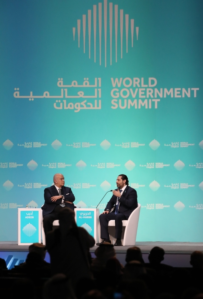 Lebanese Prime Misister Saad Hariri (R), speaks with journalist Emad El-Din Adeeb during the opening session of the World Government Summit in Dubai on Sunday. — AFP