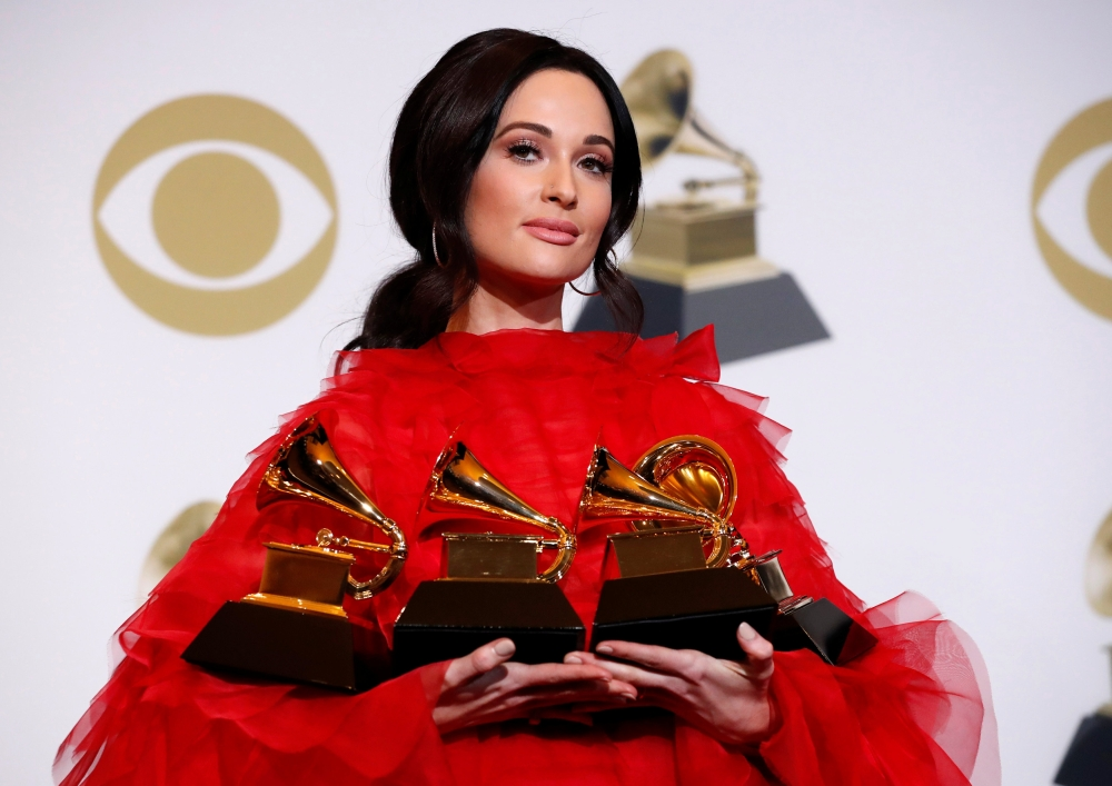 Kacey Musgraves poses backstage with her four awards, including for Album of the Year for