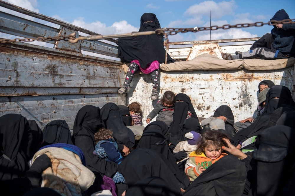 """Women and children fleeing from the last Daesh group's tiny pocket in Syria sit in the back of a truck near Baghuz, eastern Syria. More than four years after the extremists declared a """"caliphate"""" across large parts of Syria and neighboring Iraq, several offensives have whittled that proto-state down to a tiny holdout. — AFP"""