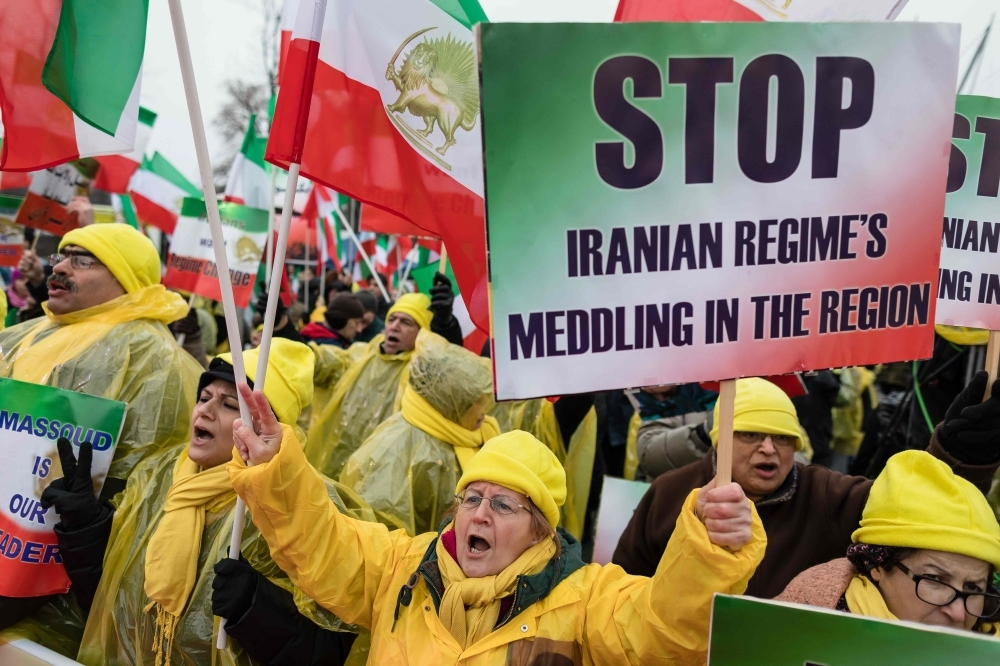 People demonstrate with banners and placards during a rally in Warsaw on Wednesday in supporters of the National Council of Resistance of Iran, demanding tougher policy on Iran and its violation of human rights. — AFP