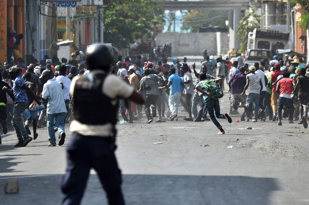 Demonstrators flee as Haitian Police open fire, during the clashes, in the center of Haitian Capital Port-au-Prince, in this Feb. 13, 2019 file photo. — AFP