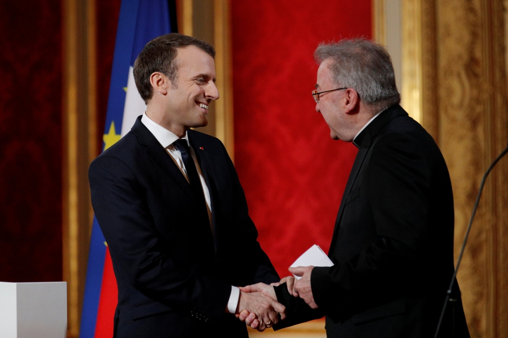French President Emmanuel Macron, left, greets Apostolic Nuncio to France Luigi Ventura, right, as he presents his New Year wishes to members of the diplomatic corps at the Elysee Palace in Paris, France, in this Jan. 4, 2018 file photo. — Reuters