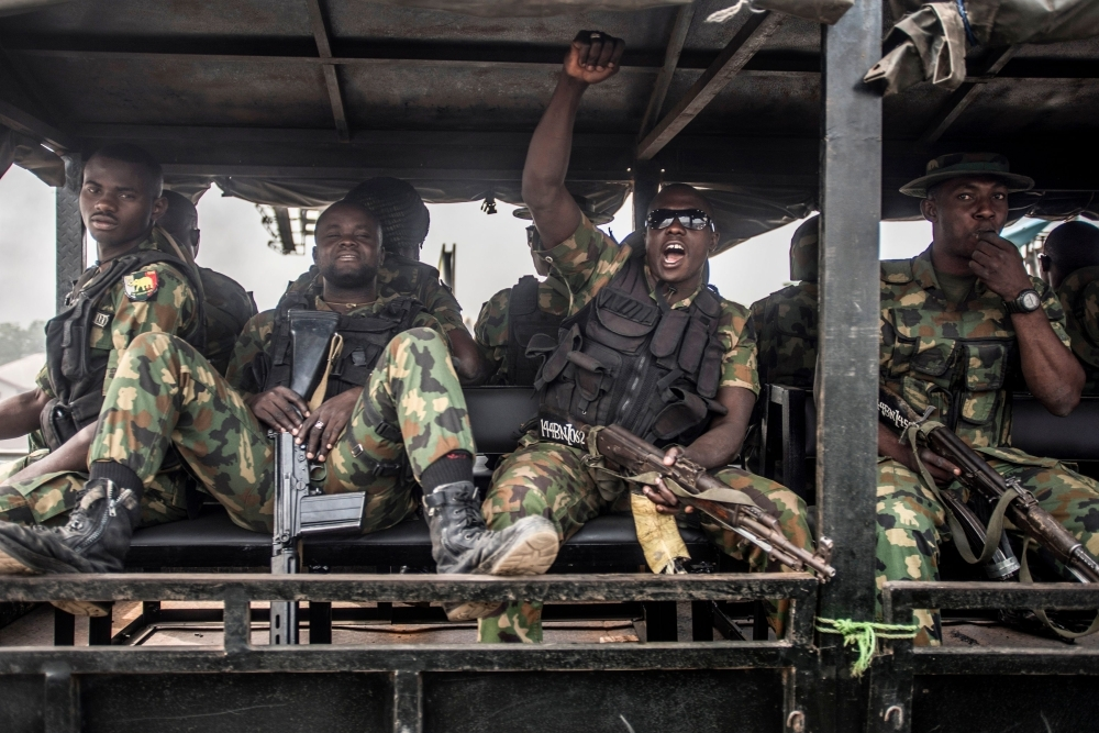 Nigerian soldiers ride in a truck during a patrol of Aba, a city in southern eastern Nigeria and a stronghold for pro-biafran separatists, during a military patrol on Friday, one day ahead Nigerian elections. — AFP