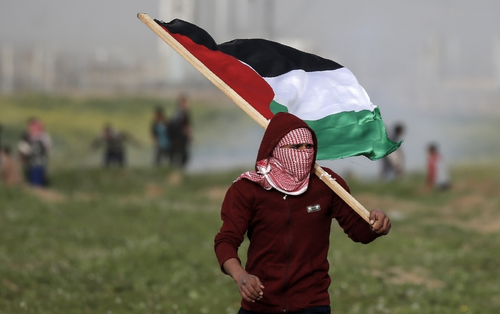 A masked Palestinian protester carries the national flag during clashes with Israeli forces following a demonstration near the fence along the border with Israel, east of Gaza City, on Friday. — AFP