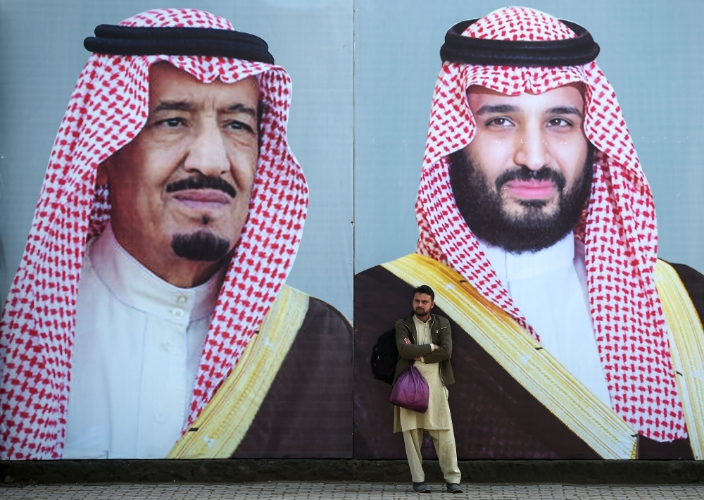 A Pakistani man waits for transport in front of billboards showing portraits of Custodian of the Two Holy Mosques King Salman and Crown Prince Muhammad Bin Salman displayed on a street ahead of the Crown Prince's arrival in Islamabad. — AFP